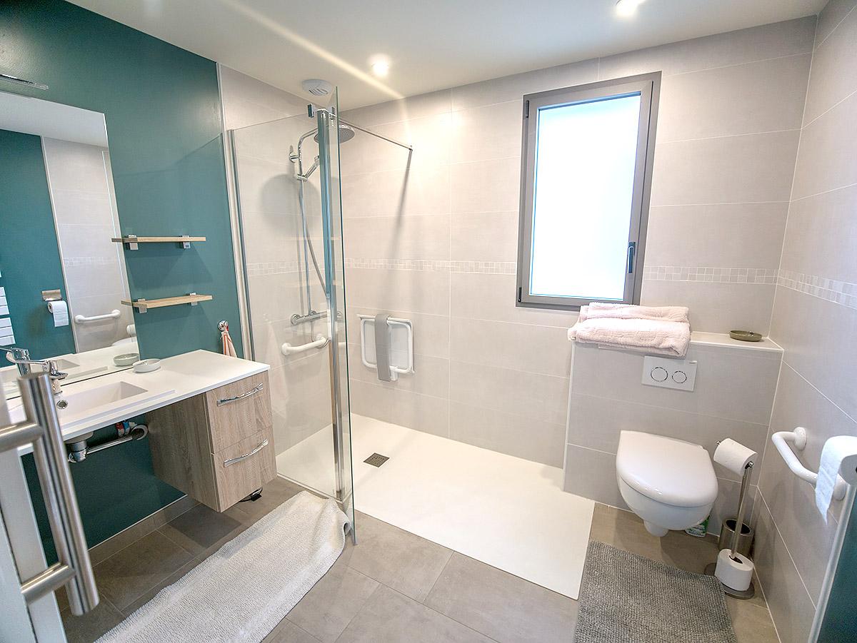 La chambre du rez-de-chaussée propose une grande salle de douche PMR.