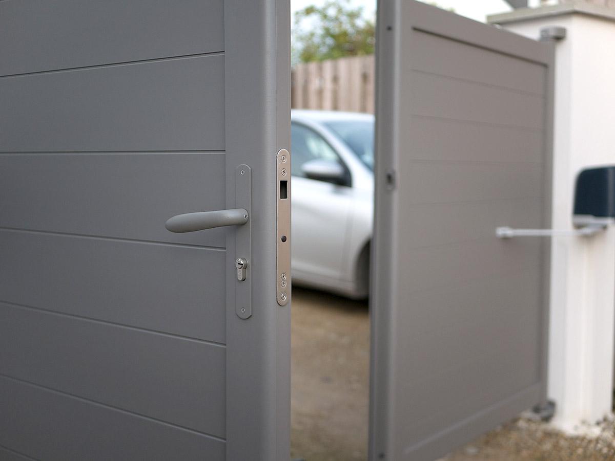 Portail automatique et parking privé avec rampe d'accès.